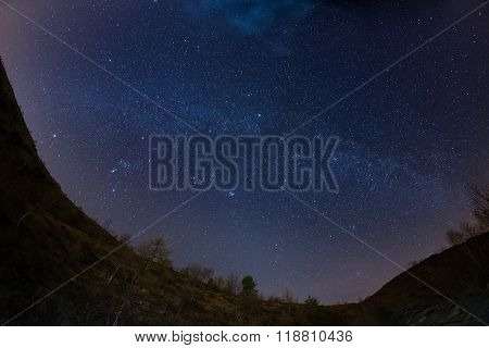 The starry sky and Milky Way captured on the Alps by fisheye lens with scenic distortion and 180 degree view. Andromeda The Pleiades Orion and Sirio clearly visible. Low digital noise. stock photo