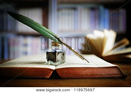 Quill pen and ink well resting on an old book in a library concept for literature, writing, author a