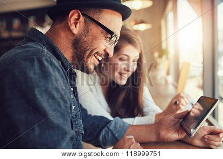 Young Couple Using A Digital Tablet Together At A Coffee Shop