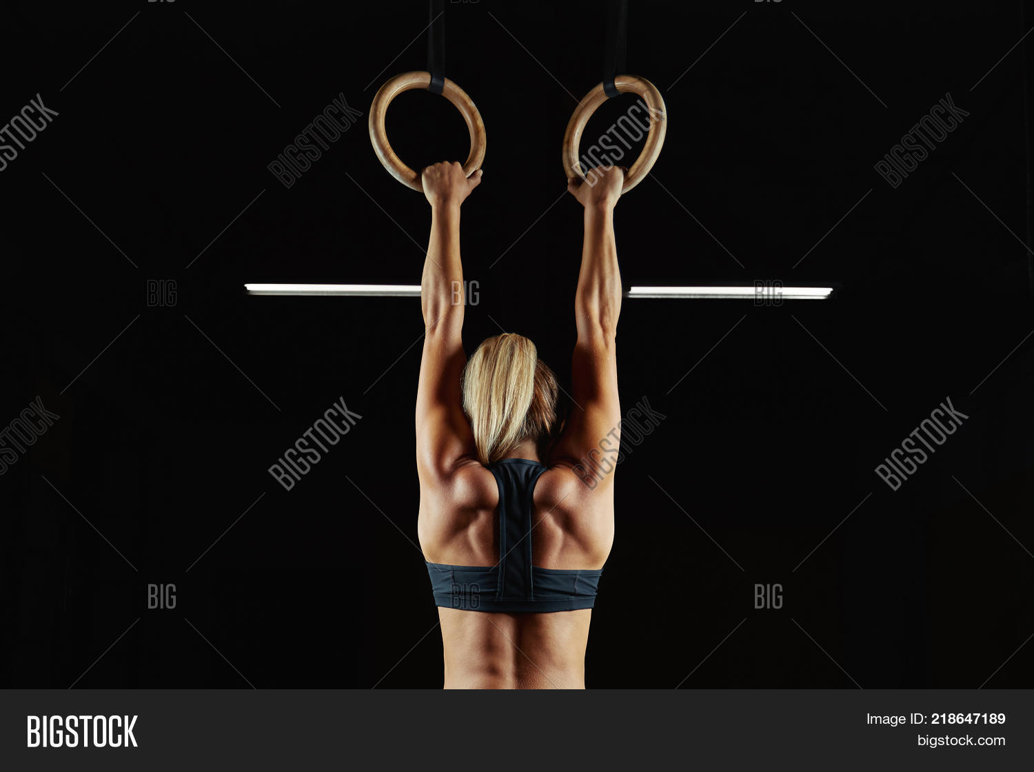 Full length rearview shot of a female athlete performing pull-ups on gymnastic rings. Fitness woman with strong beautiful body exercising on gym rings health power endurance competitive