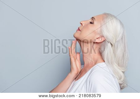 Close up portrait of senior attractive pretty nice woman with beaming smile holding having applying anti-aging for dry skin cream lotion over grey background stock photo