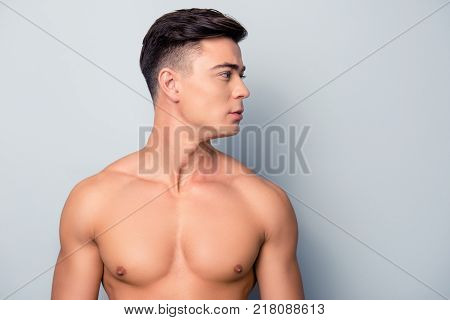 Portrait of confident concentrated handsome muscular with perfect ideal skin shaven guy isolated on grey background stock photo