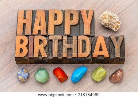 Happy Birthday greeting card in vintage letterpress wood type against grained wood with colorful polished stones and gypsum rosette stock photo