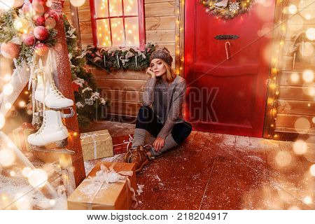 Beautiful young woman is sitting on the porch of a house decorated for Christmas. Time for miracles. Merry Christmas and Happy New Year. stock photo