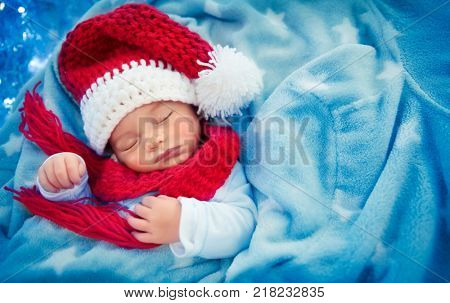 Portrait of a cute little baby boy wearing festive Santa hat and sleeping at home, covered with his blue blanket like in snow, happy Christmas holidays
