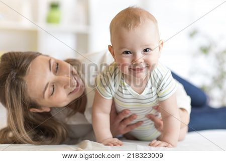 Mom and baby boy playing in sunny room. Mother and little infant kid relaxing at home. Family having fun together.