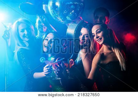 Dance party with group people dancing. Women and men have fun in night club. Happy girl on foreground and disco ball on background. Illumination from rays, special effects. Opening of new strip club. stock photo