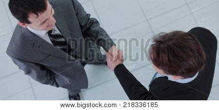 Two business people shaking hands with each other in the office stock photo