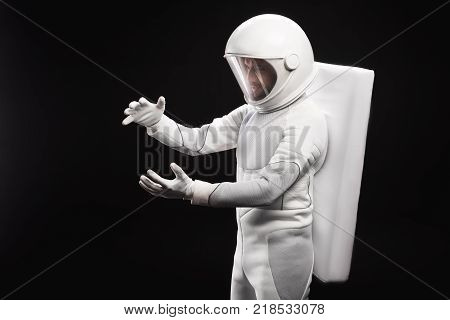 New discovery. Side view of concentrated young astronaut wearing specialized protective suit and helmet is standing and holding important unidentified object. Isolated background stock photo