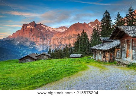 Beautiful alpine landscape, old Swiss traditional wooden hut and magical sunset with Wetterhorn peak in background, Grindelwald, Bernese Oberland, Switzerland, Europe stock photo