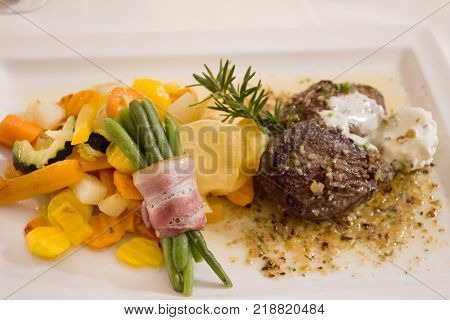 Steak beef and gravy sauce with fried vegetable mix and ham roll up long bean on ceramic plate serve dinner in restaurant at Pfunds village in Tyrol Austria stock photo