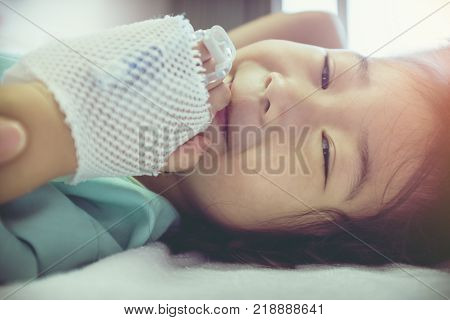 Illness asian child smiling and looking at camera with bright sunlight. Young pretty girl admitted in hospital while saline intravenous (IV) on hand. Health care stories. Vintage film filter effect. stock photo