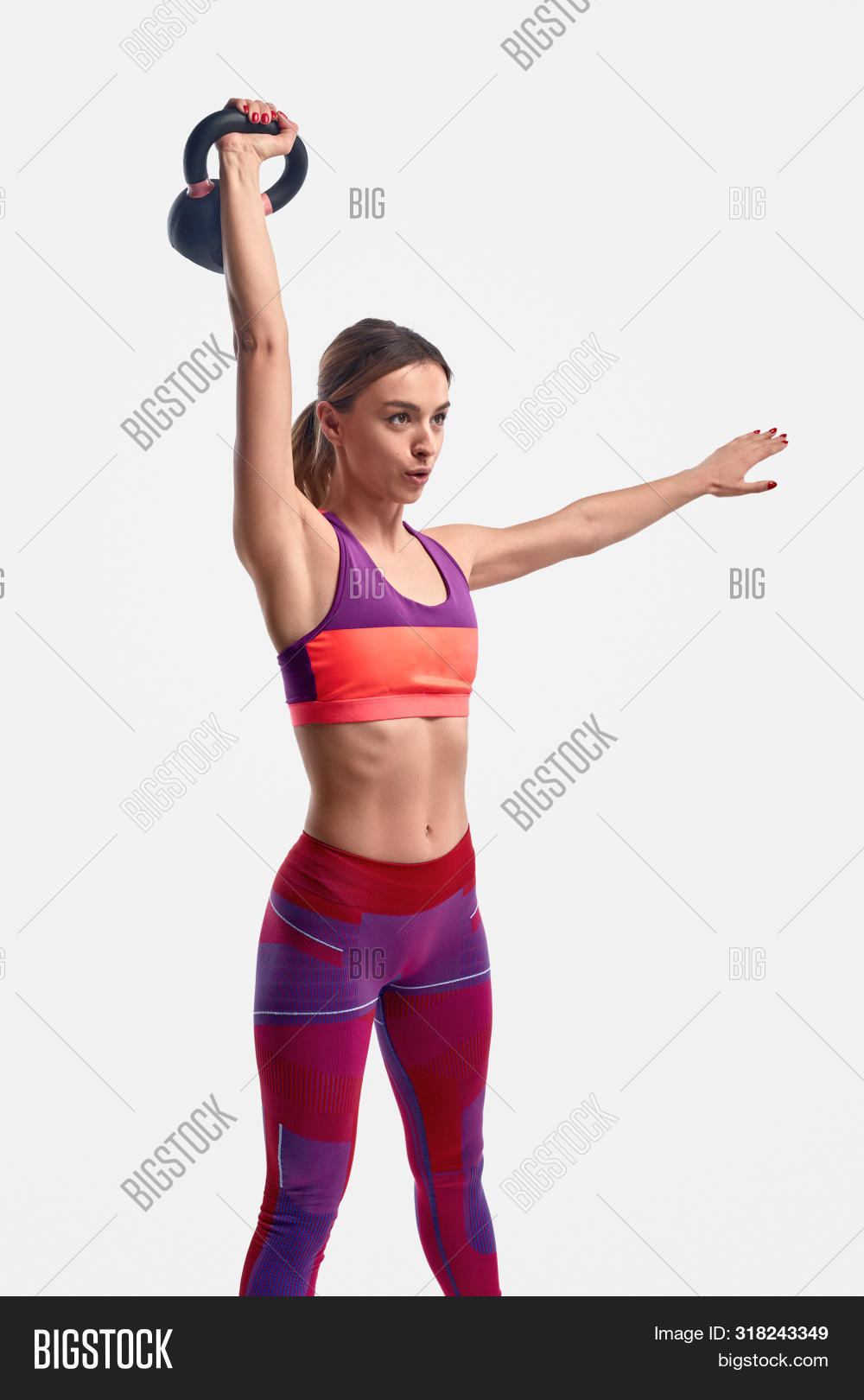 Muscular Young Female In Sportswear Lifting Heavy Kettlebell Over Head And Breathing While Exercisin