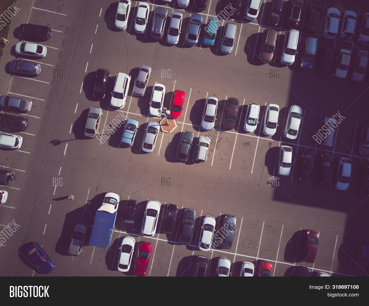 A view from above to the process of car parking. Heavy traffic in the parking lot. Searching for spaces in the busy car park. Parking advice. Cruising for parking in busy business center