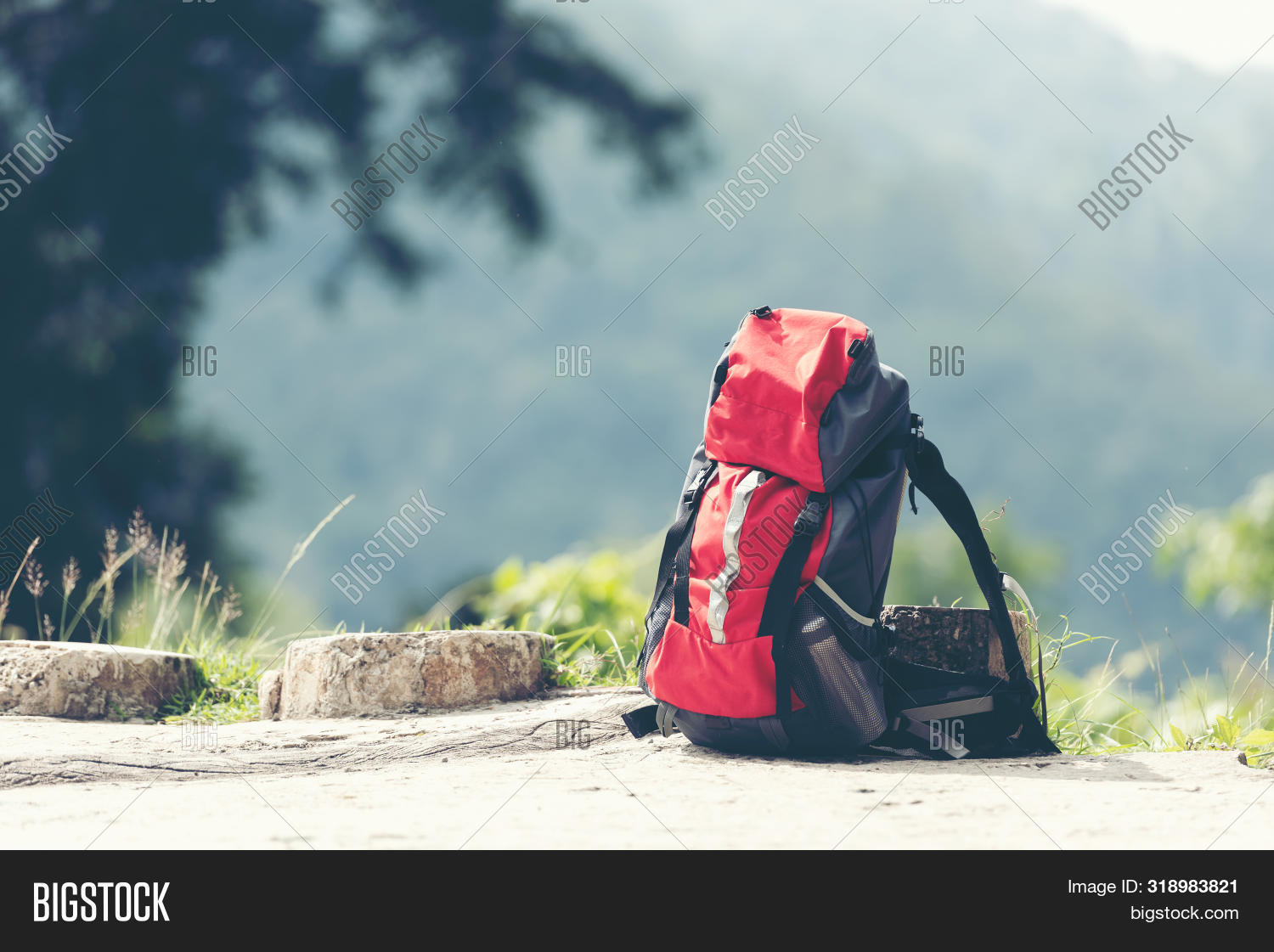 Hiking backpack travel gear on mountain. Items include hiking boots, cup, map, binoculars for travel destination and leisure in vacation. Flat lay of outdoor travel equipment items for mountain camping trip.
