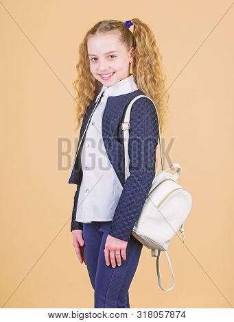Girl little fashionable cutie carry backpack. Popular useful fashion accessory. Schoolgirl with small leather backpack. Carry bag comfortable. Stylish mini backpack. Learn how fit backpack correctly stock photo