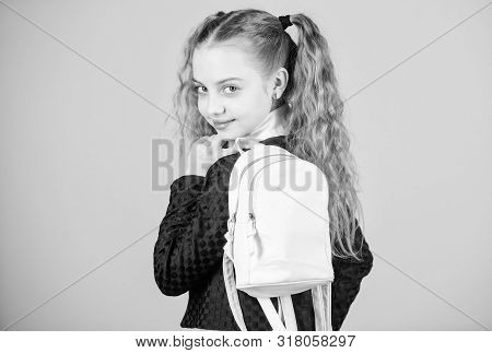 Schoolgirl ponytails hairstyle with small backpack. Carrying things in backpack. Learn how fit backpack correctly. Girl little fashionable cutie carry backpack. Popular useful fashion accessory stock photo