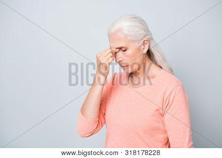Photo of sad upset suffering from acute pain in head near nose granny wearing peach color pullover isolated grey background stock photo