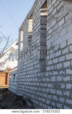 View of the back wall of the house under construction. Site on which the walls are built of gas concrete blocks stock photo