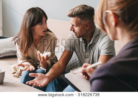 Photo of irritated unhappy couple man and woman having conversation with psychologist on therapy session in room stock photo