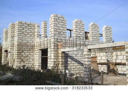 exterior of a country house under construction. Site on which the walls are built of gas concrete blocks and ladder stock photo