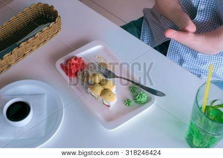 Problem of adaptation to usual life guy without wrists. Disabled man with two amputated stump hands eats sushi rolls in cafe with fork, hands closeup. Independent Invalid person with disabilities. stock photo