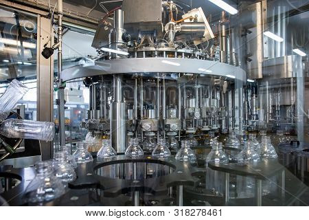 Automated Process Of Filling Plastic Bottles Inside Industrial Machine Conveyor Line Or Belt. Water
