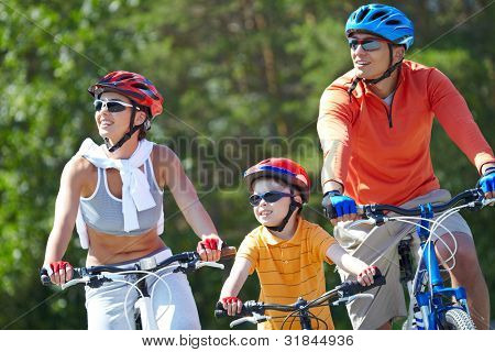Portrait of happy family riding on bicycles at leisure stock photo