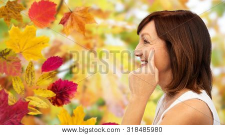 beauty, skin aging and old people concept - profile of smiling senior woman pointing to her eye wrinkles over autumn leaves and nature background stock photo