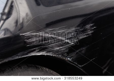 Damaged car body after a crash accident. Black vehicle wheel arch closeup. Scratches and dents. Repairs needed. stock photo