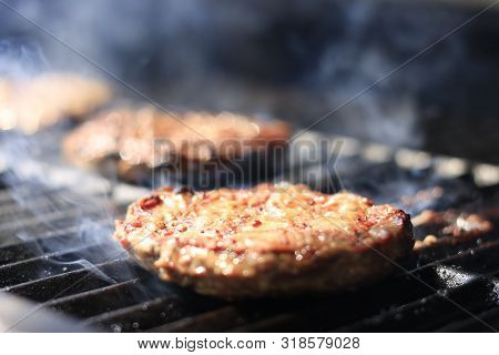 Burgers. Hamburgers being flame broiled on the gas grill stock photo