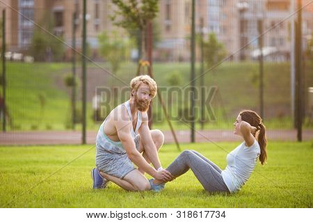 Sit ups fitness couple exercising sit up outside in grass. Fit people working out cross training. Woman doing abdominal crunches press exercise with trainer. Couple Doing Sit-Ups Abdominal Crunch stock photo