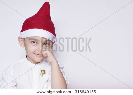 Portrait of a six-year-old middle eastern boy against the white background. Celebrating Christmas. 6-7 year old kid with Santa Claus hat. Copy space for text and ad stock photo