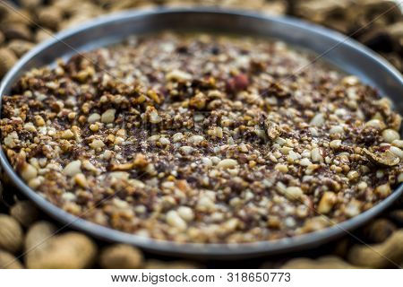 Mandvi pak, sing pak, chiki, peanut barfi or chikki in a silver colored plate along with roasted peanuts and some raw also on the wooden surface. stock photo