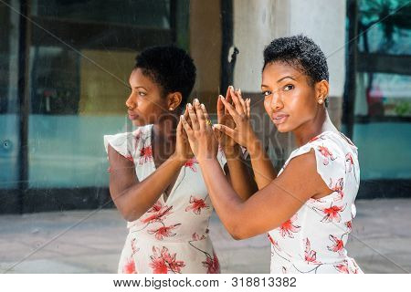 Young African American Woman with short afro hairstyle, standing by mirror in New York, hands touching reflections, head turning around, thinking. Concept of self assured, self esteem, self checking. stock photo