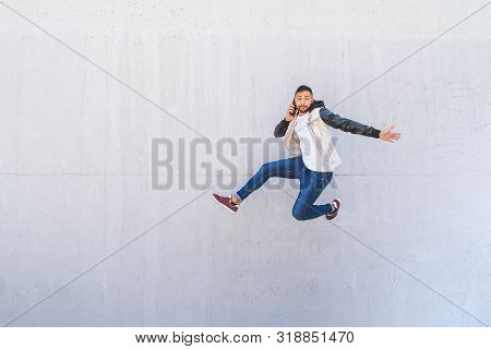 Latin American Man Jumping Excited on a Wall Background . Man Wearing a Hat Jumping in the Street. Handsome Guy Jumping of Happiness Outdoor. stock photo