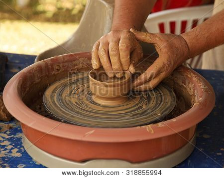 Hands of a potter sculpt clay dishes on a pottery wheel. Folk craft for making dishes. Creation of a ceramic product. Teaching ancient craft. Utensils for everyday life. History of folk art. Dirty han stock photo