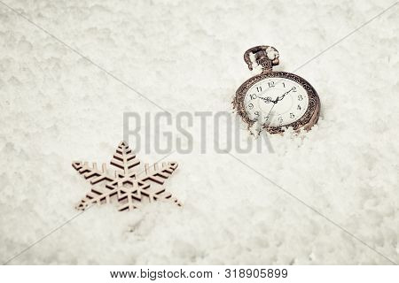 Vintage golden pocket watch  and toy snowflakes on snow. New Year time. Concept for New Year or Merry Christmas. Holiday winter vintage background. stock photo