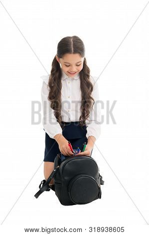 Carrying things in backpack. Getting ready. Fit backpack correctly. Girl little fashionable cutie carry backpack. Popular useful fashion accessory. Schoolgirl ponytails hairstyle with small backpack. stock photo