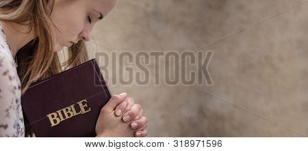 Christian worship and praise. A young woman is praying and worshiping in the evening. stock photo