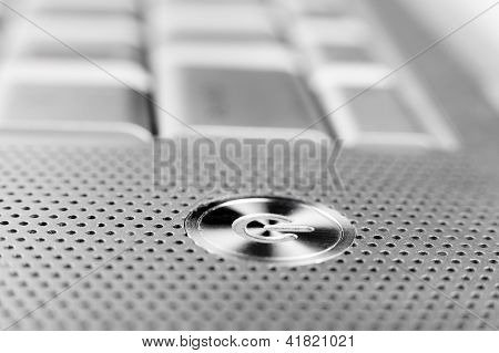 silver color laptop power button macro closeup with holes grid arround ** Note: Shallow depth of field stock photo