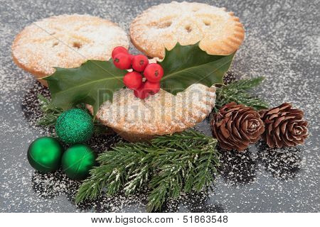 Christmas mince pie group with holly, green baubles, pine cones and winter greenery. stock photo