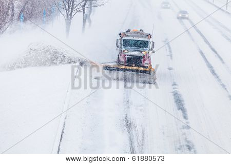 Snowplow Truck Removing the Snow from the Highway during a Cold Snowstorm Winter Day stock photo