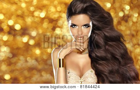 Fashion brunette girl with Long wavy hair beauty makeup luxury jewelry. Beautiful attractive young woman in dress posing over holiday lights glitter background. stock photo