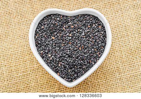 Black Sesame in white bowl on sack background. stock photo
