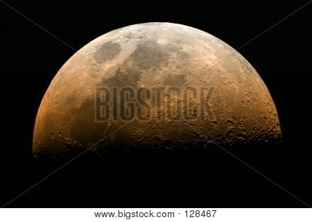 rising moon in its half moon phase with reddish color stock photo
