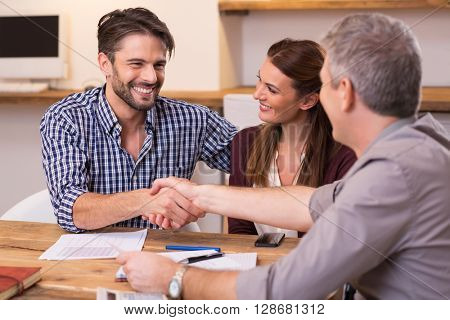 Handshake of a mature manager with a happy young couple at office. Businessmen handshake during meet