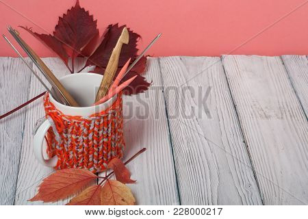 Autumn still life cup of coffee on wooden table. nitted sweater with autumn leaves, spokes, crochet and coffee mug. Autumn moody style background. Top view stock photo