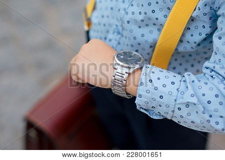 Silver watch on the hand of future businessman in blue shirt, with brifcase and yellow suspenders. Time on wrist watch. Man with clock checks the time. Hand with clock. stock photo