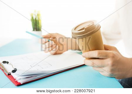 Male hands holding pen, writing. Side view on man on trendy color blue desk. Man and stilish workplace. Business concept stock photo